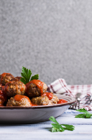 Traditional spicy meatballs in tomato sauce on wooden background. Selective focus.