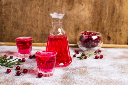 Transparent red drink in a glass on wooden background. Selective focus.