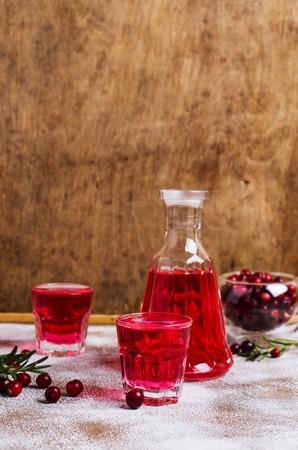 alcoholismo: Bebida roja transparente en un vaso sobre fondo de madera. Enfoque selectivo