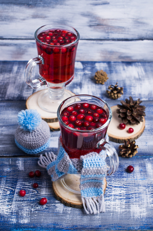 Transparent cranberry tea in glass on wooden background. Selective focus.