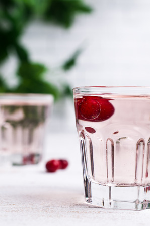 Transparent pink drink with cranberry in the glass on a light background. Selective focus.