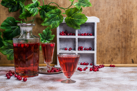 destilacion: Transparent red drink with cranberries on a wooden background. Selective focus.