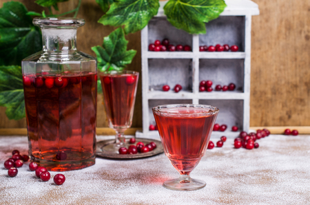 Transparent red drink with cranberries on a wooden background. Selective focus.