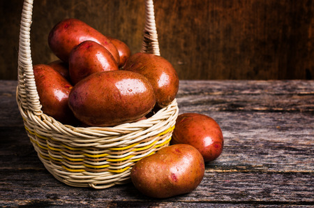 Large washed potatoes in a box on wooden background. Selective focus.