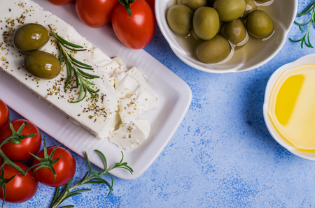 Cheese feta with olives and rosemary on a concrete background. Selective focus.