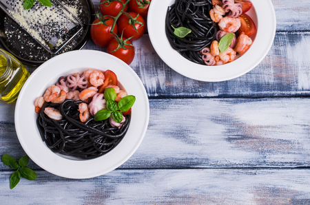 Black spaghetti with seafood and tomatoes in a plate. Selective focus. Stock Photo