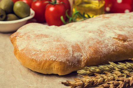 Traditional ciabatta bread on a wooden background with spices and vegetables. Selective focus. Stock Photo