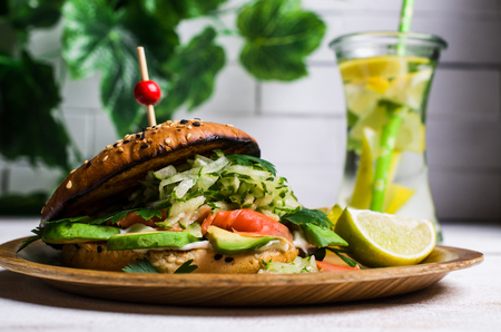 Burger with salted salmon and vegetables on wooden background. Selective focus. Stock Photo