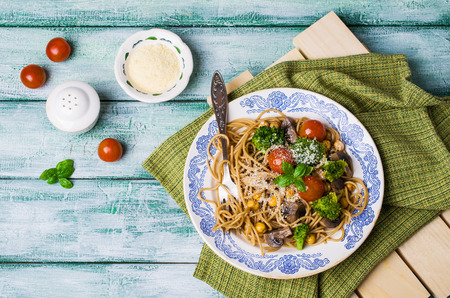 Dark pasta with vegetables, mushrooms and chickpeas in a bowl on a wooden table. Selective focus. Stock Photo