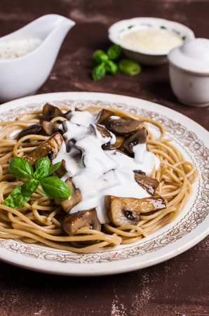 Dark spaghetti with mushrooms and white sauce in a plate on the table. Selective focus.