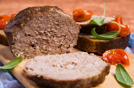 Traditional meatloaf with spices and vegetables on the table. Selective focus.