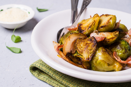 Fried Brussels sprouts with bacon in a bowl on the table. Selective focus. Stock Photo