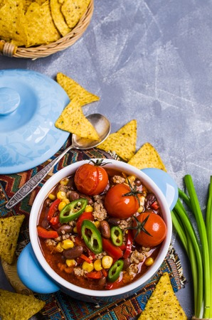 Traditional Mexican chili con carne on the table with vegetables and nachos. Selective focus. 스톡 콘텐츠