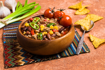 Traditional Mexican chili con carne on the table with vegetables and nachos. Selective focus. Stockfoto
