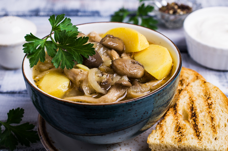 Transparent soup with oyster mushrooms and vegetables in a plate on a wooden background. Selective focus. Stock Photo