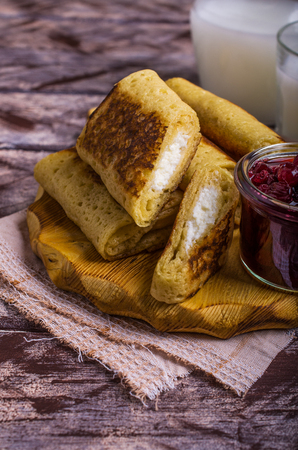 Pancakes with white filling and berry confiture in plate on wooden background. Selective focus.
