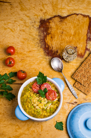 Thick soup with lentils, peas and tomatoes on a wooden background. Selective focus.