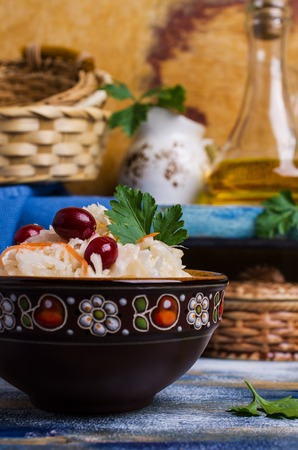 Sauerkraut with carrots and cranberries in bowl on wooden background. Selective focus.