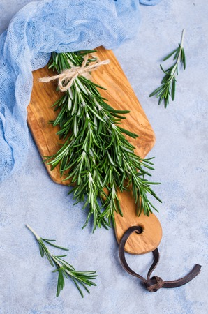Branches of raw rosemary on wooden cutting Board. Selective focus. Stock Photo