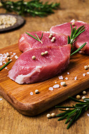 Raw slice of meat with spices and rosemary on wooden background. Selective focus. 写真素材