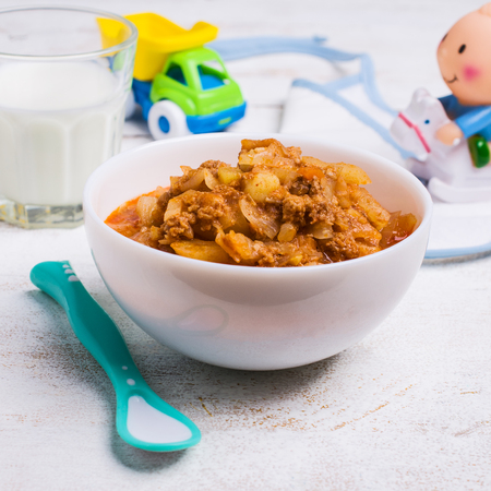 Thick soup for baby food with vegetables and meat in a bowl on wooden background. Selective focus.
