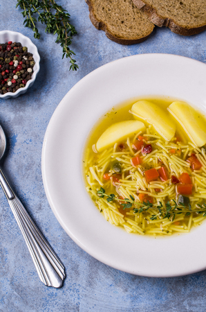 Soup with pasta and vegetables in bowl on stone background. Selective focus. Banque d'images