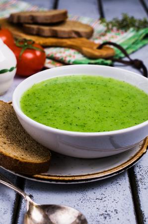 テーブルの上のボウルにグリーンクリームスープ。選択的な焦点。