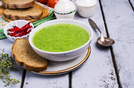 Green cream soup in a bowl on the table. Selective focus. 写真素材