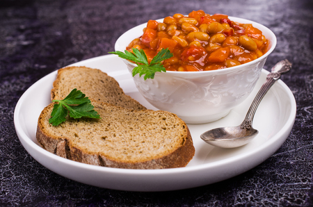 Stewed beans with vegetables in tomato sauce in a plate on the table. Selective focus. Stock Photo