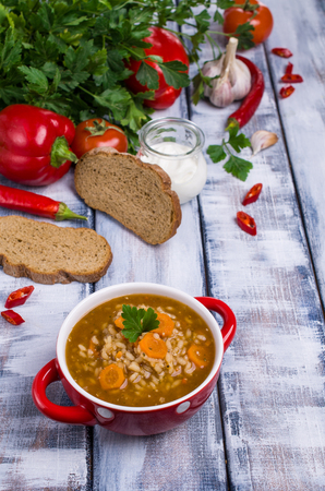 Traditional spicy soup with rice and vegetables in a plate on the table. Selective focus. Stock Photo