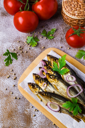Small smoked fish with vegetables and spices on wooden background. Selective focus.