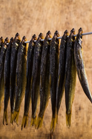 Small smoked fish on thick wire on wooden background. Selective focus.