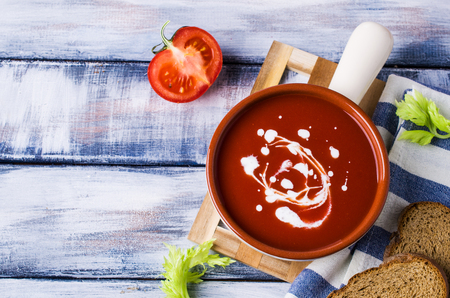 Traditional tomato soup with cream in a plate on the table. Selective focus. Stock Photo