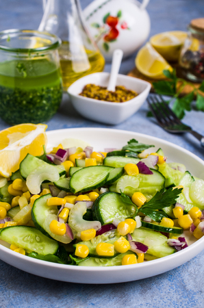 Salad with raw vegetables and corn in a plate on the table. Selective focus.