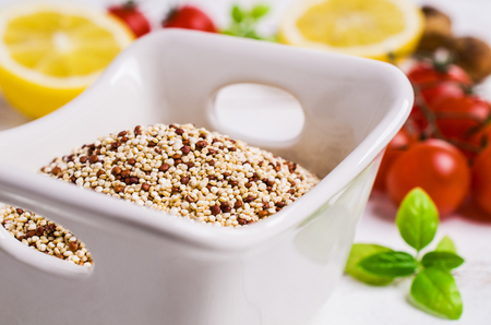 Dry mixture of quinoa grains on wooden background with tomatoes and lemon. Selective focus. Stock Photo