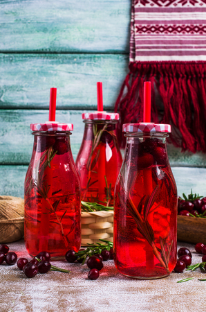 Transparent red drink of berries in glass on wooden background. Selective focus.