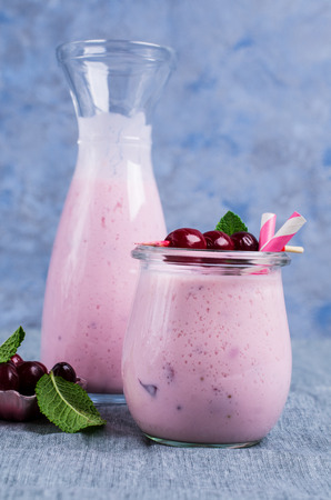 Milkshake with cranberry and mint in glass on the table. Selective focus.