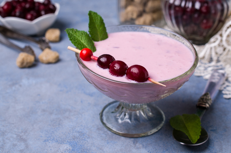 Cold dairy pink soup with berries in glass on the table. Selective focus. Stock Photo