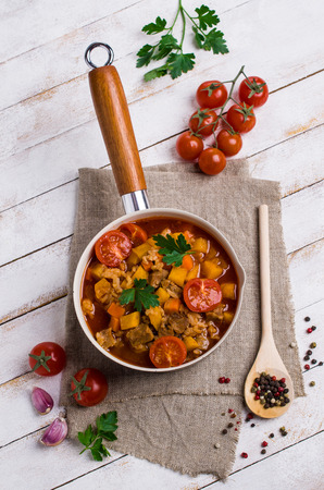 Thick soup with meat, rice and vegetables on wooden background. Selective focus.