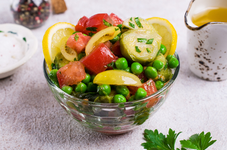 Salad with raw slices of vegetables in a dish on the table. Selective focus. Stock Photo