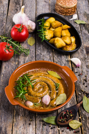 Fried round sausages with vegetables and spices on wooden background. Selective focus.