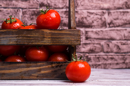 Raw tomatoes with water drops in a box on a wooden background. Selective focus.
