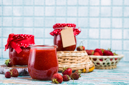 Red strawberry jam in glass jar on wooden background. Selective focus.