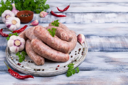 Thick meat sausages in a natural shell with spices on a wooden background. Selective focus.
