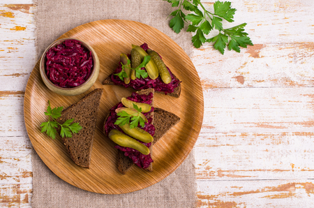 Sandwiches with beet and pickled cucumber on dark bread on a wooden background. Selective focus.