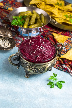 Traditional beet dip with sesame seeds in a dish on the table. Selective focus.