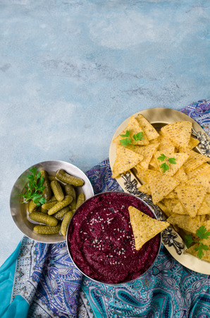 Traditional beetroot dip on a background of pickles and corn chips. Selective focus.