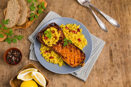 Baked Butternut squash with spicy rice on wooden background. Selective focus. Stockfoto