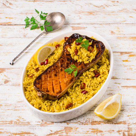 Baked Butternut squash with spicy rice on wooden background. Selective focus. Standard-Bild