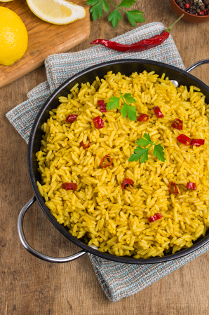 Traditional spicy rice in a plate on a wooden background. Selective focus.
